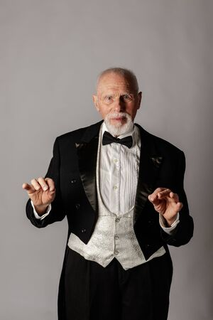 Old man in a tailcoat. Portrait of a bearded old man. Senior man dressed in a tailcoat on gray background.