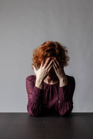 Sad red-haired woman is sitting at the table. Depression and sadness.