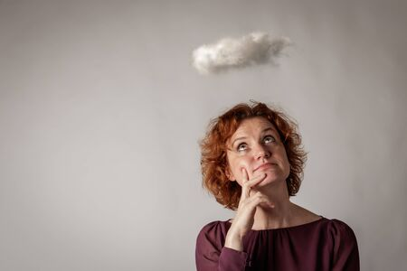 Red-haired woman and cloud. Woman is dreaming or thinking about something. Looking up. Stock Photo
