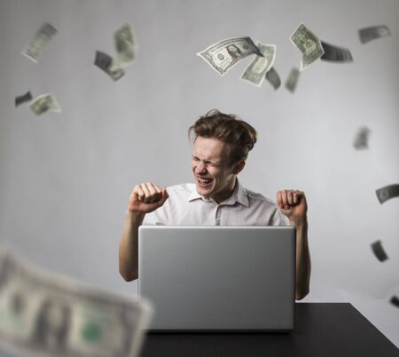 Young happy man with laptop and falling dollar banknotes. Young man using a laptop to browse the net. Currency, success and lottery concept.