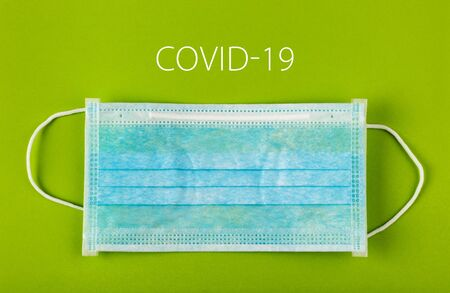 Medical protective mask on green background. Surgical face mask. coronavirus outbreak concept. Covid-19