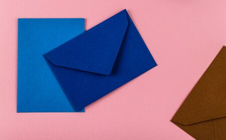 Colorful envelopes on a pink background. Mail envelopes on the table.