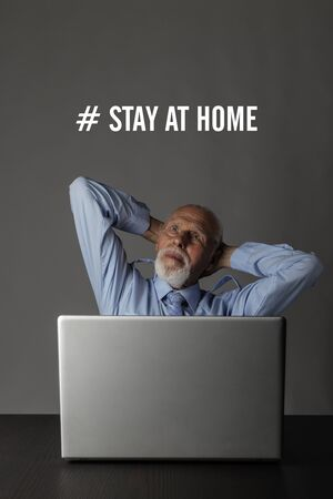 Old man is staying at home during the COVID-19 coronavirus outbreak. Senior worried about the Coronavirus and working from home. Stay at home social media campaign for coronavirus prevention. Social distancing and Quarantine concept.
