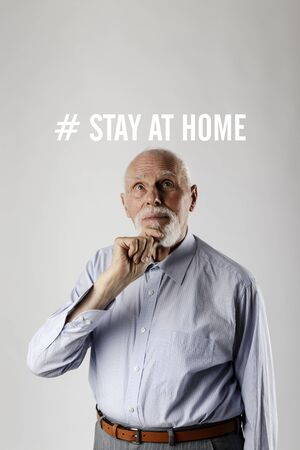 Old man is staying at home during the COVID-19 coronavirus outbreak. Senior worried about the Coronavirus. Stay at home social media campaign for coronavirus prevention. Social distancing and Quarantine concept.