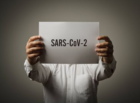 Man is holding white paper with text - SARS-CoV-2. Man and Covid-19. COVID-19 crisis and self-isolation concept. 版權商用圖片