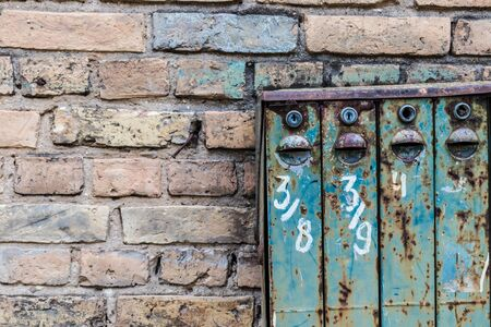 Old Soviet-style mailboxes. Old metal and numbered mailboxes on brick wall. Correspondence.