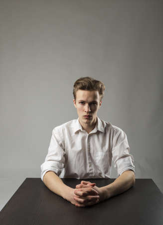 Young man in white is full of doubts and hesitation. Doubt and dream concept. Serious man.