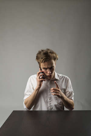 Young man talking on the phone. Communication and anger. Banque d'images