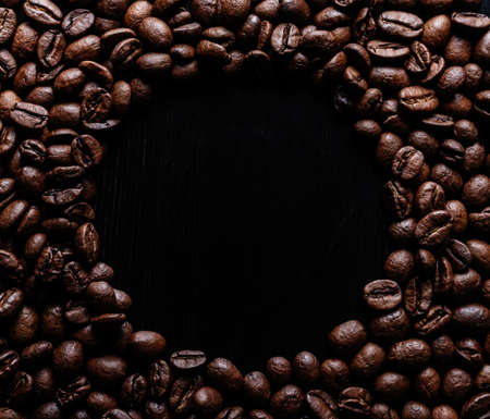 Circle frame of roasted brown coffee beans on wooden background. Background with space for text top view.