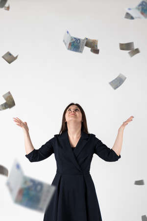 Rejoicing. Woman in blue and falling Euro banknotes. Success, currency and lottery concept.