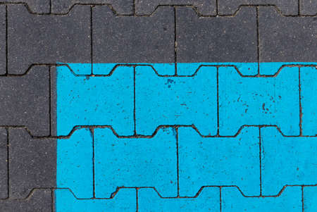 Parking place. Parking for people with disabilities. Blue color painting on brick floor as background. Texture. Imagens