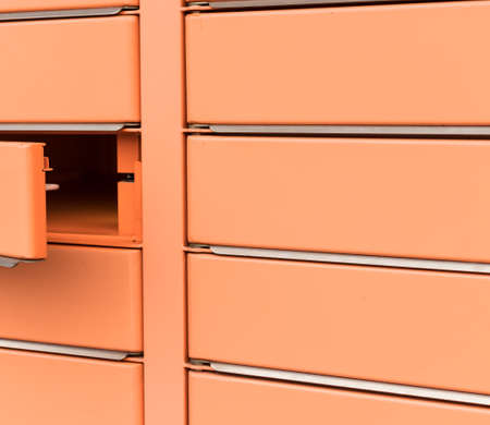 Post office box, the door is open. Orange post box for rentals. Post box lockers for parcels that the recipient can pick up there.