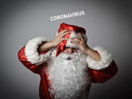 Frustrated Santa Claus and suffering from headache. Concept about coronavirus outbreak. COVID-19 crisis concept. Text about Coronavirus. Stockfoto