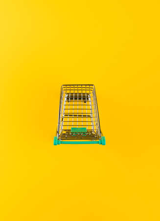 Metallic shopping cart trolley on yellow color background with copy space. Shopping symbol.