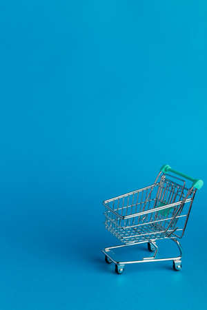 Metallic shopping cart trolley on blue color background with copy space. Shopping symbol.