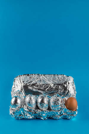 Eggs in aluminum foil on blue background with copy space. Difference and diversity concept.