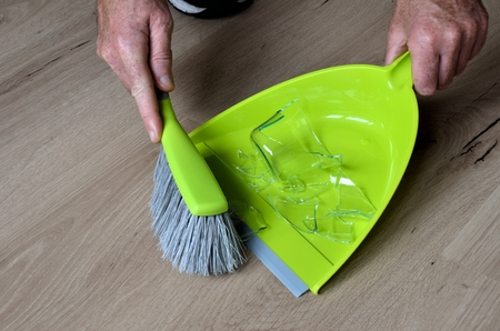 Clean up broken water glass with broom and dustpan