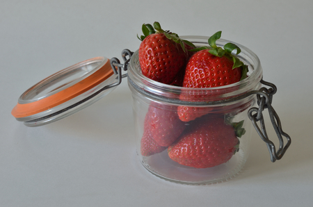Red strawberries in open old glas jar on white background Reklamní fotografie