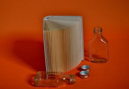 Open standing book and liquour bottles on orange background Imagens