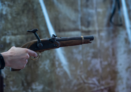 Hands of man in vintage clothing holding muzzle loading musket. Before the shot Stock Photo
