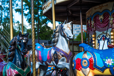 turnabout: Beautiful horse Christmas carousel in a holiday park. Horses on a traditional fairground vintage carousel. Merry-go-round with horses.
