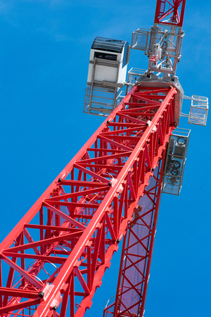buildingsite: Red truck crane boom with hooks and scale weight above blue sky Stock Photo