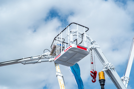 hydraulic lift: Hydraulic lift platform with bucket of yellow construction vehicle, heavy industry, blue sky and white clouds on background