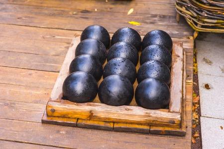 Wet black cannonballs lie on the ground