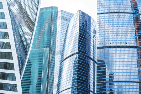 Bottom view of modern skyscrapers in business district in evening light at sunset with lens flare filter effect Stok Fotoğraf