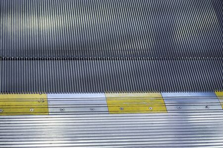 going up a shiny metal staircase, escalator, empty, finished with blue tine