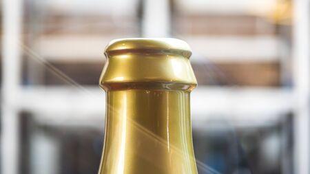 Golden Bottleneck of a champagne. Bottle on gradient grey background