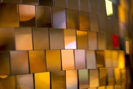 Colorful square metallic tiles on a wall or floor. Blue, green, teal, yellow, orange, purple reflective tile pattern. Shiny tile pattern with purple, teal, green, blue, yellow, gold and orange Stock fotó