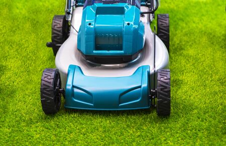 Turquoise lawn mower on grass.