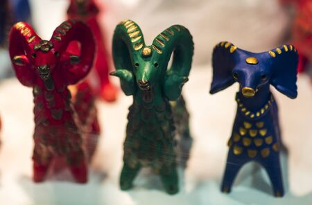 Beautiful vintage colourful wooden dymkovo dolls at market. Baphomet dolls is folks cultural symbol of Satanic cult. With selective focus on one doll
