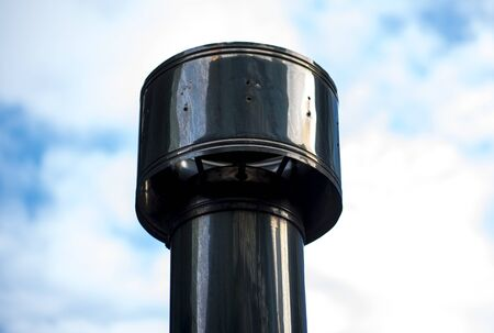 Detail of a chimney on factory against of blue sky. Chimney with steel pipes.