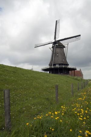 Mening bij een windmolen - Oude windmolen op de dijk bij medemblik- Nederland