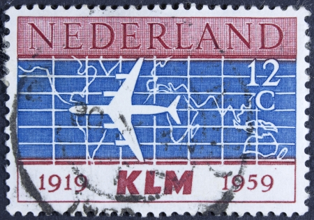 NETHERLANDS - CIRCA 1959  A stamp printed in the Netherlands issued for the 40th anniversary of K L M   Royal Dutch Airlines  shows silhouette of Douglas DC-8 Airliner and World Map, circa 1959   photo