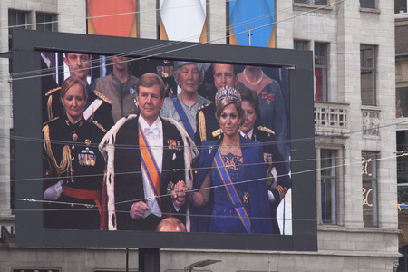 orange nassau: AMSRTERDAM, APRIL 30-2013: King alexander and queen maxima during the inauguration on a great tv screen on dam square