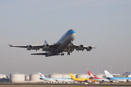 ascended: Amsterdam the Netherlands 18 february 2015: Of the runway ascended blue Boeing 747 of the Royal Dutch Airlines KLM. In the background kerosene tanks and parked aircrafts.