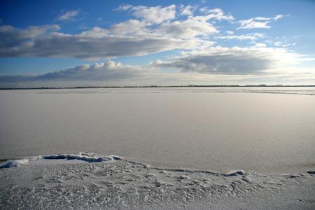 ijsselmeer: Frozen IJsselmeer with clouds and blue skies on a beautiful sunny winter day. Stock Photo