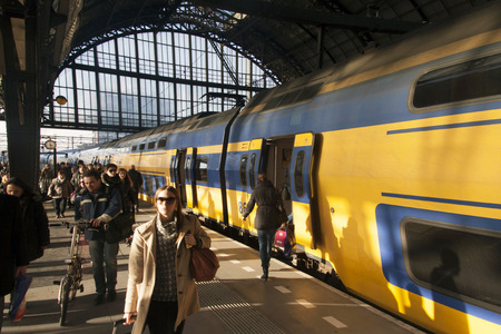 Amsterdam, Holland - february 4.2014: Just arrived dutch ns train with passengers alighting on Amsterdam central station. Editorial
