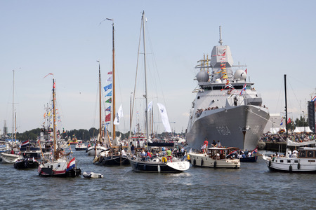 historic world event: AMSTERDAM, THE NETHERLANDS, 20 AUGUST 2015: Boats with visitors to the sail with a large Dutch navy ship falling on the great nautical event SAIL