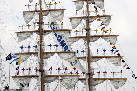 historic world event: Port of Amsterdam, Noord-Holland, Netherlands - August 19, 2015: Sailors on the masts of the tall ship Arc Gloria from Colombia constantly sail in 2015