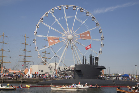 historic world event: AMSTERDAM, THE NETHERLANDS, 20 AUGUST 2015: People sail in boats along submarine and a Ferris wheel falling on the great nautical event sail
