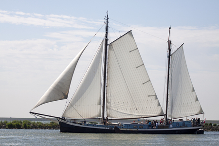 onboard: traditional wooden sailing ship under sail leaving the port with onboard tourists
