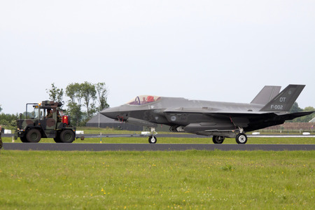replaces: LEEUWARDEN, THE NETHERLANDS - JUNE 11 2016: joint Straight F 35 fighter was towed to the hangar after a demonstration flight. this replaces the F16 at the Dutch Air Force