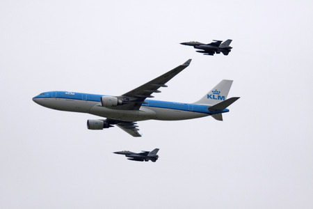 LEEUWARDEN, THE NETHERLANDS - JUNE 11 2016: Dutch KLM Boeing escorted by two F16 aircraft of the Dutch air force Editorial