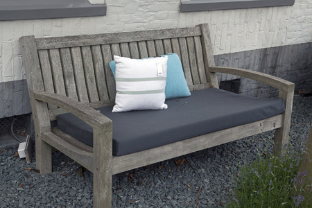 elegantly: Gray wooden bench with cushions for relaxing.