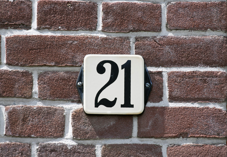 enameled: Enameled house number twenty one on a red brick wall