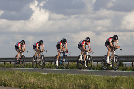 ENKHUIZEN, THE NETHERLANDS - JULY 2, 2016: Cyclists ride in a row, during a time trial contest for cyclists on the car dike Lelystad and Enkhuizenon july 2, 2016 in Enkhuizen